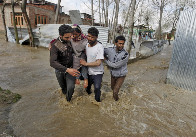A woman is carried to a safer place from her partially submerged house after incessant rains in Srinagar March 30, 2015. (Photo by Danish Ismail/Reuters)