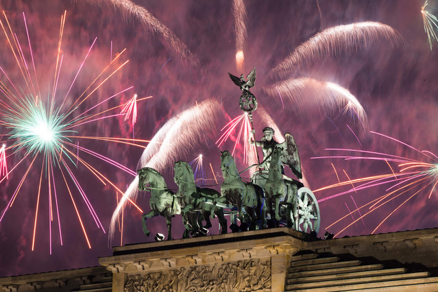 Fireworks explode behind the quadriga of Berlin' s landmark Brandenburg Gate to usher in the New Year on January 1, 2017. (Photo by Odd Andersen/AFP Photo)
