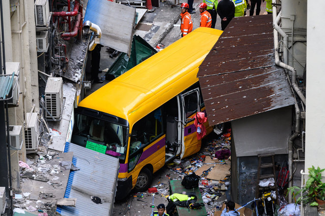 Police officers and rescuers are seen at the accident site after a school bus rolled down a street and crashed to a standstill, killing four people and injuring 11 others, in North Point, Hong Kong, China on December 10, 2018. (Photo by Imaginechina/Rex Features/Shutterstock)