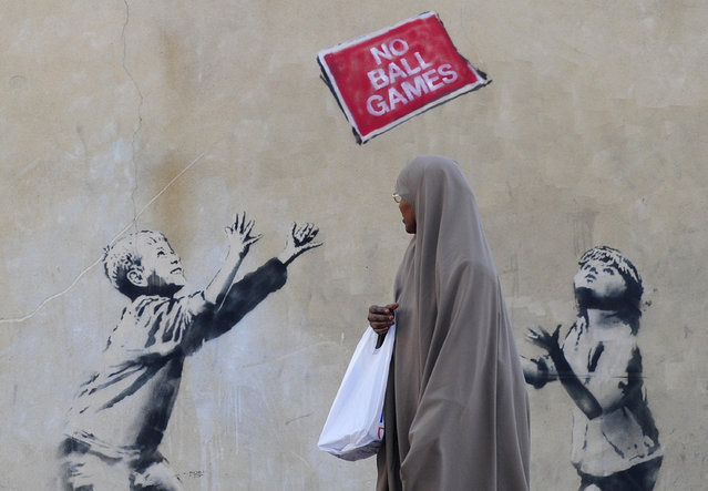 A pedestrian passes graffiti art on a wall in north London, September 24, 2009. British media have attributed the work to Banksy. (Photo by Toby Melville/Reuters)