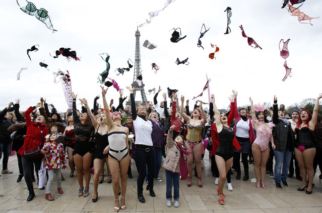 Women throw their bras up in the air during the 6th edition of the Pink Bra Bazaar Rally at Trocadero Square next to the Eiffel tower on March 29, 2015 in Paris, France. Pink Bra Bazaar is a charitable organization that aims to educate about breast health and supports women with breast cancer. (Photo by Chesnot/Getty Images)