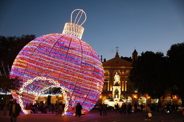 People walk by a giant christmas ball displayed in Nice, southeastern France, on December 4, 2013. (Photo by Valery Hache/AFP Photo)