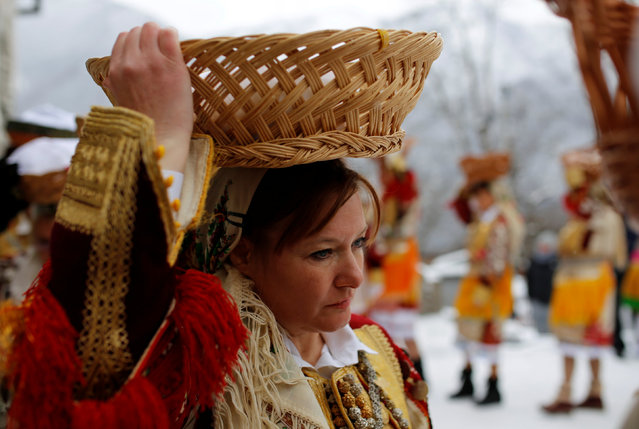 A woman dressed in a traditional folk costume balances a basket of bread on her head during Epiphany day celebration in Bitushe village, Macedonia January 19, 2017. (Photo by Ognen Teofilovski/Reuters)