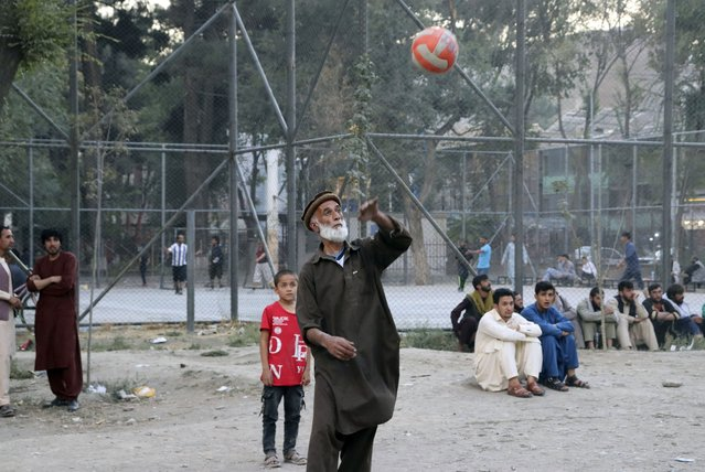 Afghans play volleyball at Shahr-e-Now Park in Kabul, Afghanistan, Monday, August 30, 2021. Many Afghans are anxious about the Taliban rule and are figuring out ways to get out of Afghanistan. But it's the financial desperation that seems to hang heavy over the city. (Photo by Khwaja Tawfiq Sediqi/AP Photo)