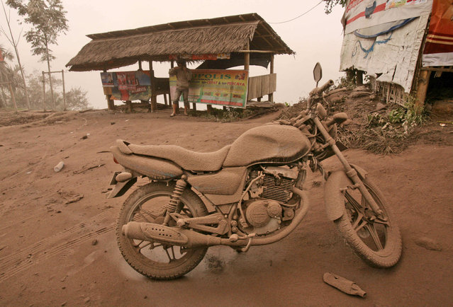 A motorcycle is covered in volcanic ash from an eruption of Mount Sinabung in Tiga Pancur, North Sumatra, Indonesia, Saturday, January 4, 2014. The 2,600-meter (8,530-foot) volcano has sporadically erupted since September. (Photo by Binsar Bakkara/AP Photo)