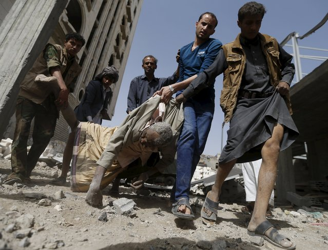 People carry the body of a man killed by an air strike on a Scud missile base in Yemen's capital Sanaa April 20, 2015. The air strike on a Scud missile base in Sanaa caused a big explosion that blew out windows in homes, killing seven civilians and wounding dozens, medical sources told Reuters. (Photo by Khaled Abdullah/Reuters)