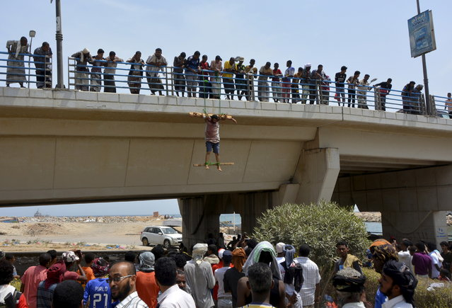 People look at a man, who residents said was killed by al Qaeda militants, hanging on a bridge in Yemen's southeastern city of Mukalla June 17, 2015. Al Qaeda militants in Yemen killed two alleged Saudi spies, residents said, accusing them of planting tracking devices which enabled the assassination of the group's leader in a suspected U.S. drone strike. (Photo by Reuters/Stringer)
