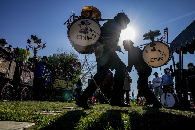 Traditional dancers, and the family of late organ grinder and ¨Chinchinero¨ Hector Lizana, 93, who died from COVID-19 three weeks after his son Manuel also succumbed to COVID-19, dance during his funeral at a cemetery in Santiago, Chile, Wednesday, September 15, 2021. A Chinchinero is an urban street performer in Chile, who plays a bass drum-type percussion instrument with long drumsticks strapped to his back which also involves a rope with a noose tied around the performer's foot to play the cymbals which also form part of this improvised instrument. (Photo by Esteban Felix/AP Photo)