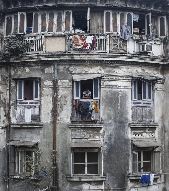 A resident looks out of a window of an apartment of an old residential building in Mumbai February 13, 2014. The cost for buying a residential apartment in Mumbai close to the city centre ranges from 12,000 Indian rupees ($ 200) per square feet to 112,552 Indian rupees ($ 1800) per square feet. (Photo by Danish Siddiqui/Reuters)