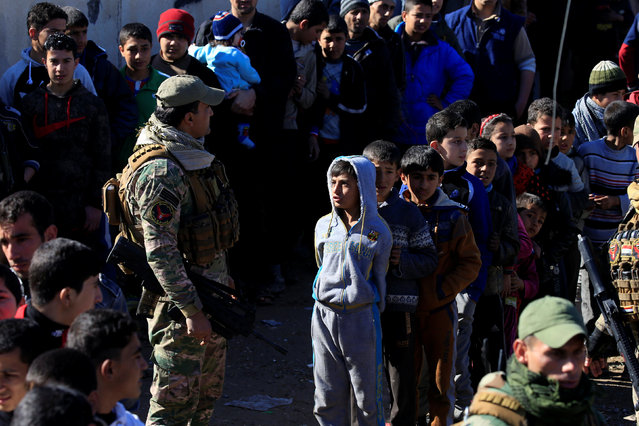 Displaced children and youth who fled the clashes queue to receive aid from Iraqi security forces in Antesaar neighborhood of Mosul, Iraq, January 24, 2017. (Photo by Alaa Al-Marjani/Reuters)