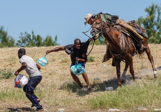 A United States Border Patrol agent on horseback tries to stop a Haitian migrant from entering an encampment on the banks of the Rio Grande near the Acuna Del Rio International Bridge in Del Rio, Texas on September 19, 2021. The United States said Saturday it would ramp up deportation flights for thousands of migrants who flooded into the Texas border city of Del Rio, as authorities scramble to alleviate a burgeoning crisis for President Joe Biden's administration. (Photo by Paul Ratje/AFP Photo)