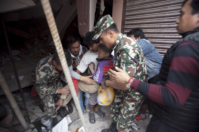 Volunteers carry an injured boy after rescuing him from the debris of a building that was damaged in an earthquake in Kathmandu, Nepal, Saturday, April 25, 2015. (Photo by Niranjan Shrestha/AP Photo)