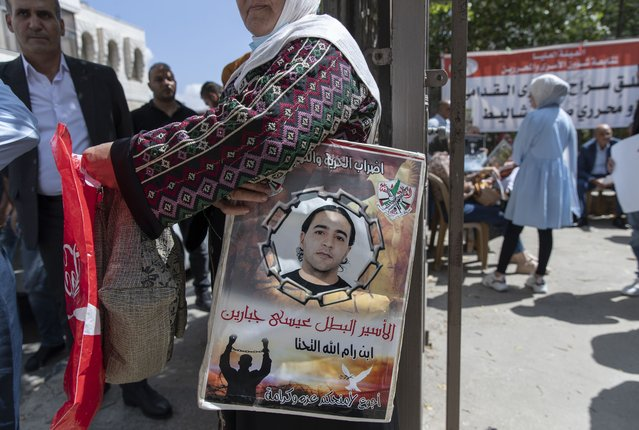 """A woman holds a poster with a picture of a Palestinian prisoner that reads """"the prisoner hero Issa Jabbareen, I starve for your dignity and pride"""" during a protest supporting prisoners, in the West Bank city of Ramallah, Tuesday, September 14, 2021. Hundreds of thousands of Palestinians have passed through a military justice system designed for a temporary occupation that is now well into its sixth decade. Nearly every Palestinian has a loved one who has been locked up in that system at some point, and imprisonment is widely seen as one of the most painful aspects of life under Israeli rule. (Photo by Nasser Nasser/AP Photo)"""