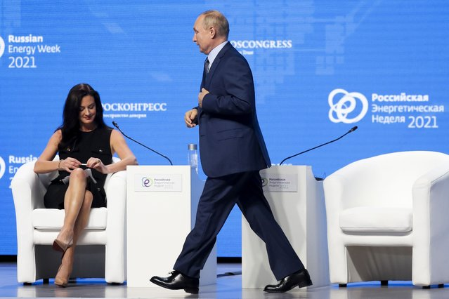 Russian President Vladimir Putin walks past CNBC's anchor Hadley Gamble during the plenary session of the Russian Energy Week in Moscow, Russia, Wednesday, October 13, 2021. (Photo by Sergei Ilnitsky/Pool Photo via AP Photo)