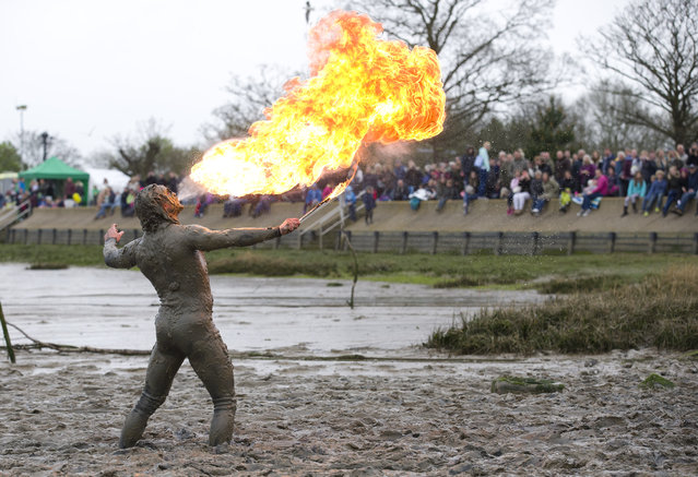 A participant blows a ball of fire after crossing the finish line during the annual Maldon Mud Race in Maldon, east England, on April 26, 2015. Originated in 1973, the race involves competitors racing around a course through the River Blackwater in Essex at low tide. (Photo by Justin Tallis/AFP Photo)