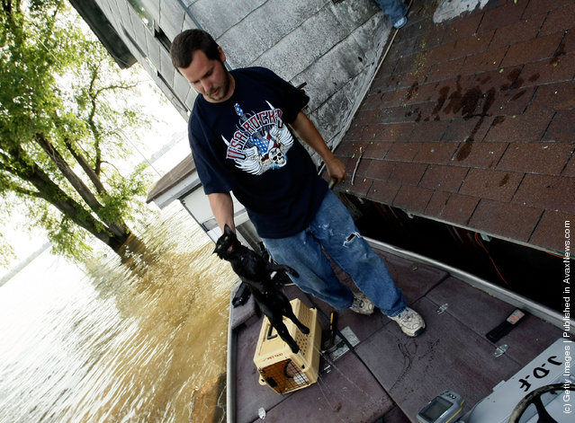 Jerry Ford rescues a wet cat from a house June 18, 2008 as floodwaters overtake the town of Oakville, Iowa