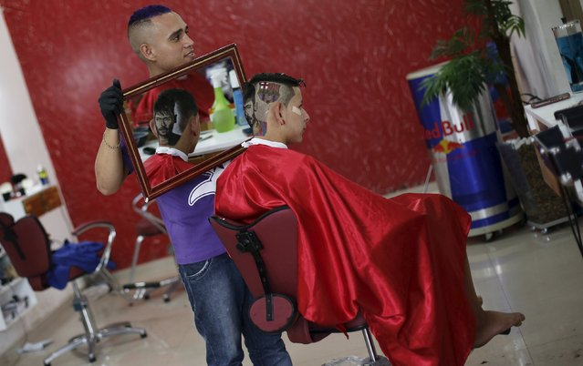 Hair artist and barber Nariko, 27, holds up a mirror so that customer Luiz Fernadez, 15, can see the image of Barcelona's Neymar and his team's badge shaved onto his head, before the Champions League semifinal first leg soccer match between Barcelona and Bayern Munich at a barbershop in Sao Vicente, near Santos, in Sao Paulo state May 6, 2015. (Photo by Nacho Doce/Reuters)