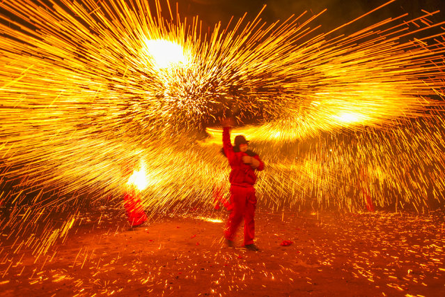A folk artist makes a shower of sparks with molten iron during a local celebration ahead of the Chinese Lantern Festival, in Luzhou, Sichuan province, China February 18, 2019. (Photo by Reuters/China Stringer Network)