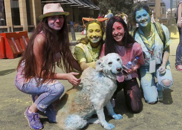 "People pose with a dog covered in colour powder during the first color run called ""Alwan LB"" in Beirut May 3, 2015. (Photo by Mohamed Azakir/Reuters)"