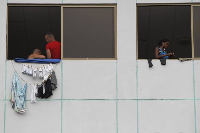 Cuban migrants are seen at the windows of an old hotel used as a provisional shelter in Paso Conoa, at the border with Costa Rica March 20, 2016. (Photo by Carlos Jasso/Reuters)
