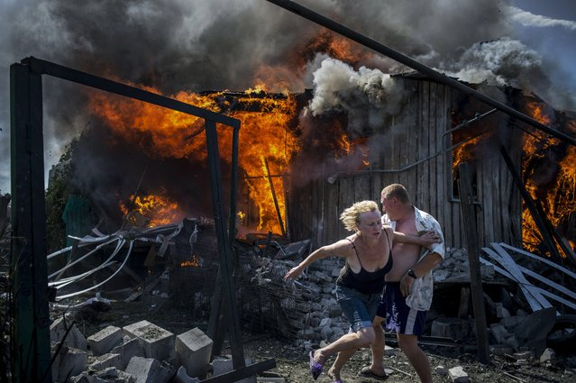 A handout photo made available by the World Press Photo (WPP) organization on 13 February 2017 shows a picture by Rossiya Segodnya photographer Valery Melnikov that won the Long-Term Projects – First Prize award of the 60th annual World Press Photo Contest, it was announced by the WPP Foundation in Amsterdam, The Netherlands on 13 February 2017. Caption: Civilians escape from a fire at a house destroyed by an air attack in the Luhanskaya village. Story: Ordinary people became victims of the conflict between self-proclaimed republics and the official Ukrainian authorities from 2014 onwards in the region of Donbass. Disaster came into their lives unexpectedly. These people were involved in the military confrontation against their will. They experienced the most terrible things: the death of their friends and relatives, destroyed homes and the ruined lives of thousands of people. (Photo by Valery Melnikov/EPA/Rossiya Segodnya/World Press Photo)