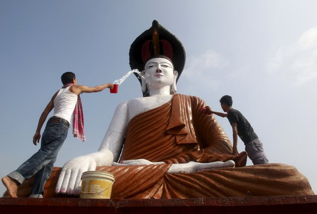 Men clean a statue of Lord Buddha in a temple on the eve of the Buddha Purnima festival, also known as Vesak Day, in Agartala, India, May 3, 2015. The festival commemorates the birth, enlightenment and death of Buddha. (Photo by Jayanta Dey/Reuters)