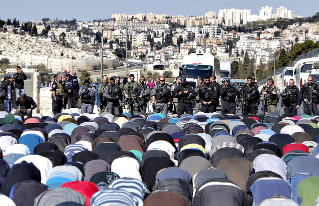 Muslim Palestinians take part in Friday noon prayers blocked by Israeli police in East Jerusalem neighborhood of Ras al-Amud, on February 28, 2014. Clashes broke out following Friday noon prayer three days after police clashed with stone-throwing Palestinians at the al-Aqsa mosque compound, hours ahead of a debate in the Israeli parliament on Jews' right to pray at the compound, which is currently denied. The flashpoint compound sits above the Western Wall plaza and houses the Dome of the Rock and the Al-Aqsa mosque, and is Islam's third-holiest site. (Photo by Ahmad Gharabli/AFP Photo)