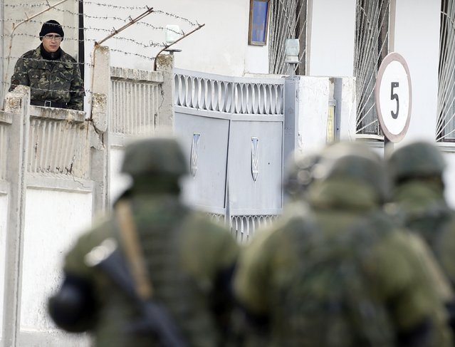 A Ukrainian serviceman watches uniformed men, believed to be Russian servicemen, passing by at a Ukrainian military base in the village of Perevalnoye outside Simferopol, March 6, 2014. Crimea's parliament voted to join Russia on Thursday and its Moscow-backed government set a referendum within 10 days on the decision in a dramatic escalation of the crisis over the Ukrainian Black Sea peninsula. (Photo by Vasily Fedosenko/Reuters)