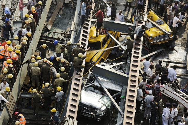 Indian rescue workers work on a partially collapsed overpass in Kolkata, India,Thursday, March 31, 2016. (Photo by Bikas Das/AP Photo)