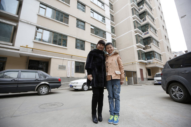 Zhang Haijing, 41, and her daughter Zhu Nuo, 11, pose for a photograph outside their apartment building in Lanzhou, Gansu province February 5, 2014. Zhang Haijing finished her education at age 23 and is a mid-level manager for Xinhua Bookstore Group. When she was a child, she wanted to become a pre-school teacher. Zhang Haijing says she wants her daughter Zhu Nuo to have a stable job, but does not mind what she does so long as she is happy. (Photo by Aly Song/Reuters)