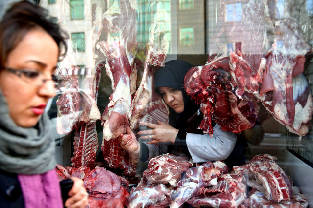 In this Tuesday, March 11, 2014 photo, butcher Zahra Shokouhi, center, works at her shop in downtown Tehran, Iran. Shokouhi, 45, a mother of three girls, learned butchery – a job held traditionally by men in Iranian society – from her husband and by working alongside him. She has surprised many passers-by in the last twelve years while working as a butcher in their shop next to a mosque in a conservative district in south of Tehran. (Photo by Ebrahim Noroozi/AP Photo)