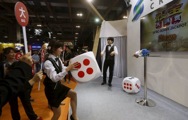 """Attendants play a """"Sic Bo"""" game with visitors at the Global Gaming Expo (G2E) Asia in Macau, China May 19, 2015. (Photo by Bobby Yip/Reuters)"""