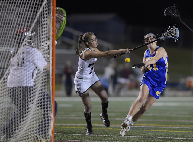 Robinson's Elli Kluegel, right, scores a 2nd half goal past  Woodson's Claire Cooke, center, and goalie Mariel Russ during Robinson's defeat of W.T. Woodson in girls lacrosse at W.T. Woodson High School in Fairfax VA,  April 15, 2016. (Photo by John McDonnell/The Washington Post)