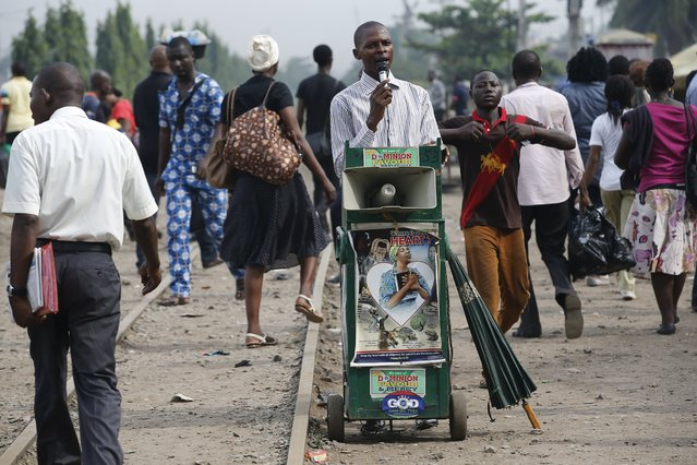 People walk past a man preaching along a train track in Ikeja district in Nigeria's commercial capital Lagos April 12, 2016. (Photo by Akintunde Akinleye/Reuters)