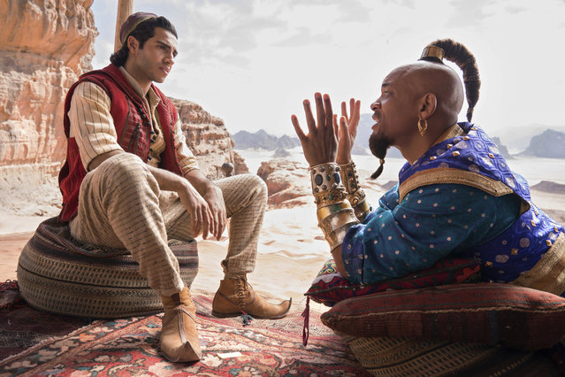 "This image released by Disney shows Mena Massoud as Aladdin, left, and Will Smith as Genie in Disney's live-action adaptation of the 1992 animated classic ""Aladdin"". (Photo by Daniel Smith/Disney via AP Photo)"