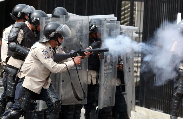 Riot policemen take positions during an anti-government protest in Caracas on April 1, 2014. In a direct challenge to President Nicolas Maduro, prominent opposition politician Maria Corina Machado vowed to take her seat in the National Assembly despite her ouster by the Supreme Court. The head of the legislative body had ordered Machado expelled and her parliamentary immunity stripped last week after she tried to speak before the Organization of American States about her country's crisis. (Photo by Federico Parra/AFP Photo)