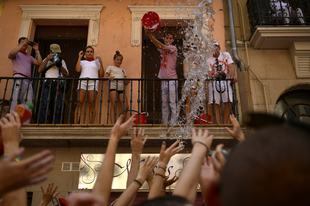 Revellers celebrate the official opening of the 2019 San Fermin fiestas in Pamplona, Spain, Saturday July 6, 2019. (Photo by Alvaro Barrientos/AP Photo)