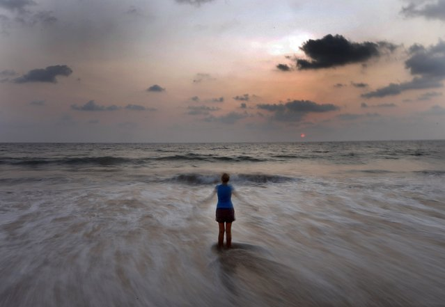 A woman performs physical exercises on a beach in Colombo March 30, 2014. (Photo by Dinuka Liyanawatte/Reuters)