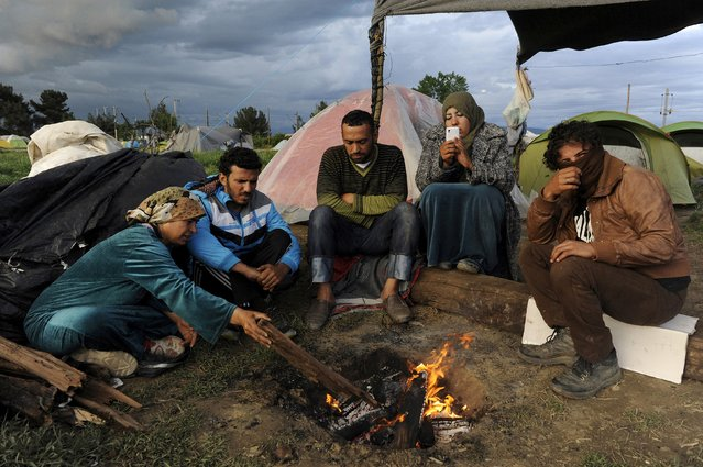 Migrants and refugees gather by a fire at a makeshift camp at the Greek-Macedonian border near the village of Idomeni, Greece, April 25,  2016. (Photo by Alexandros Avramidis/Reuters)