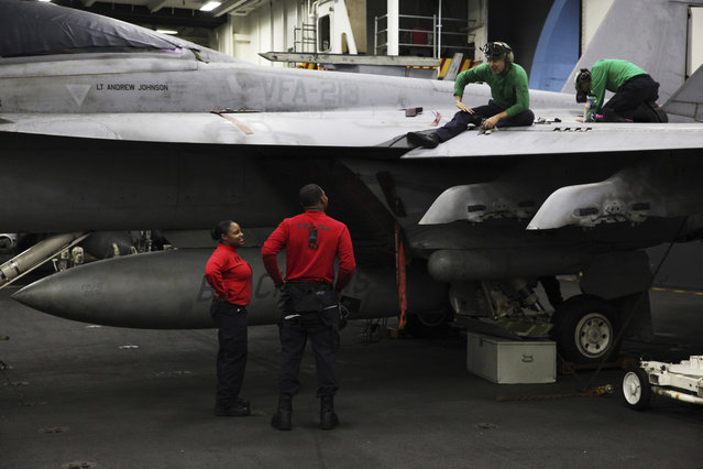 In this Tuesday, March 21, 2017 photograph, sailors work on an F-18 fighter jet on the USS George H.W. Bush as it travels through the Strait of Hormuz. (Photo by Jon Gambrell/AP Photo)