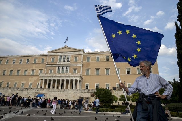 A pro-Euro protestor holds a European Union flag with a Greek national flag on top during a rally in front of the parliament building in Athens, Greece, June 30, 2015. (Photo by Marko Djurica/Reuters)