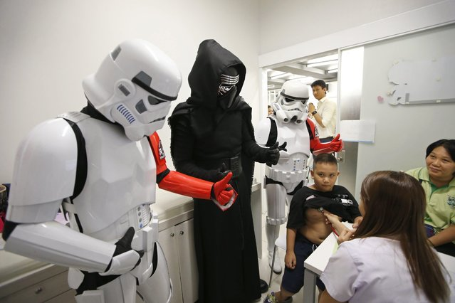 Thai Star Wars fans dressed as Kylo Ren (C) and Stormtrooper give their thumbs up to encourage a child patient who has a medical check up by a doctor during the Star Wars Day celebration at Queen Sirikit National Institute of Child Health in Bangkok, Thailand, 04 May 2016. (Photo by Rungroj Yongrit/EPA)