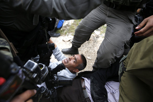 """Israeli army troops arrests a protester during a protest to mark """"National Land Day"""" near Kiryat Arba settlement in the West Bank city of Hebron, 30 March 2017. On 30 March 1976, Palestinians declared a general strike and held large demonstrations against land expropriations by Israeli authorities in the Galilee. This day has been marked as the National Land Day, Israel killed six Palestinians and injured and detained many others on that day. (Photo by Abed Al Hashlamoun/EPA)"""