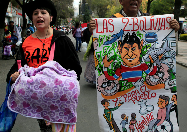 "A demonstrator with physical disabilities (R) holds a banner during a rally protest calling on the government to provide a monthly subsidy rather than an annual one in La Paz, Bolivia, May 5, 2016. The banner reads, ""A nuclear plant, what for? If they can't even pay a subsidy"". (Photo by David Mercado/Reuters)"