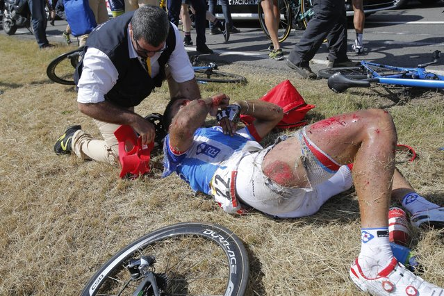 A doctor tends to William Bonnet of France after he crashed with several other riders during the third stage of the Tour de France cycling race over 159.5 kilometers (99.1 miles) with start in Antwerp and finish in Huy, Belgium, Monday, July 6, 2015. Bonnet abandoned the race following the crash. (Photo by Christophe Ena/AP Photo)