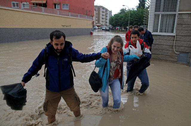 People wade through a flooded street close to the overflowing Segura river as torrential rains hit Orihuela, near Murcia, Spain, September 13, 2019. (Photo by Jon Nazca/Reuters)