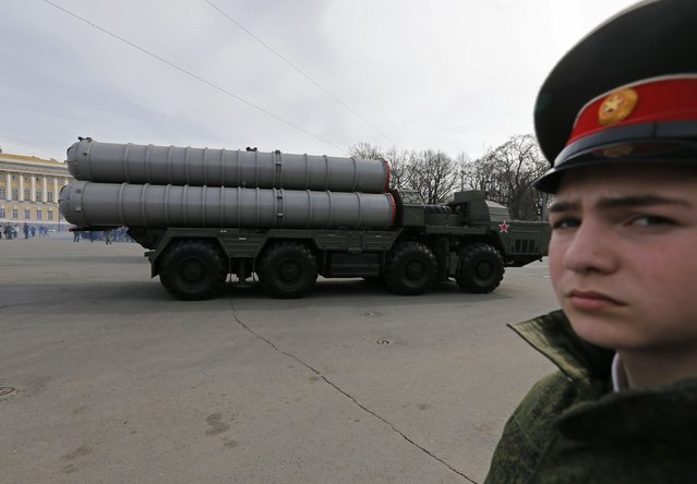 A Russian military cadet looks on as a Russian missile launcher drives pass during a rehearsal for a May 9 victory parade in Dvortsovaya Square in St. Petersburg April 28, 2014. Russia prepares to mark the 69th anniversary of the Soviet Union's victory over Nazi Germany in World War Two on May 9. (Photo by Alexander Demianchuk/Reuters)