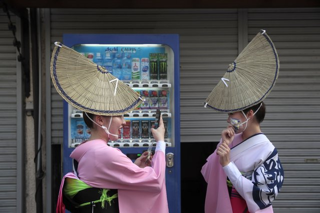 Two young dancers take pictures while waiting for the start of the Koenji Awa-Odori dance festival, in the Koenji neighborhood of Tokyo. Saturday, August 24, 2019, Started in the 1950s, the Koenji Awa-Odori has grown to be one of Tokyo's largest and most popular summer festivals an estimated 10,000 dancers participating in the dance festival. Hundreds of thousands of spectators gather in the neighborhood to watch the two-day summer spectacle. The event is held on the last weekend of August each year. (Photo by Jae C. Hong/AP Photo)