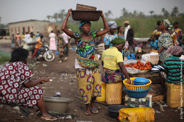 A woman carries goods while unloading her boat of produce at a market in Ganvie, near Cotonou, Benin