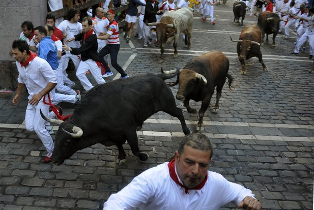 A runner sprints towards the barrier to avoid Fuente Ymbro fighting bulls at Estafeta corner during the fourth running of the bulls at the San Fermin festival in Pamplona, northern Spain, July 10, 2015. One runner was hospitalized following the run that lasted two minutes and twenty-four seconds, according to local media. (Photo by Eloy Alonso/Reuters)